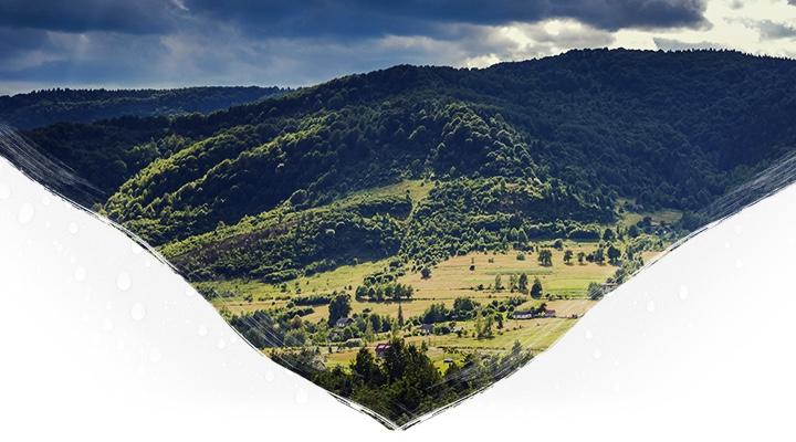 Łagodne lesiste wzgórza na tle zachmurzonego nieba i słoneczną polaną w dole