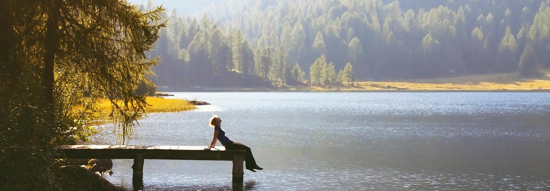 Kobieta relaksująca się na pomoście nad jeziorem otoczonym lasem