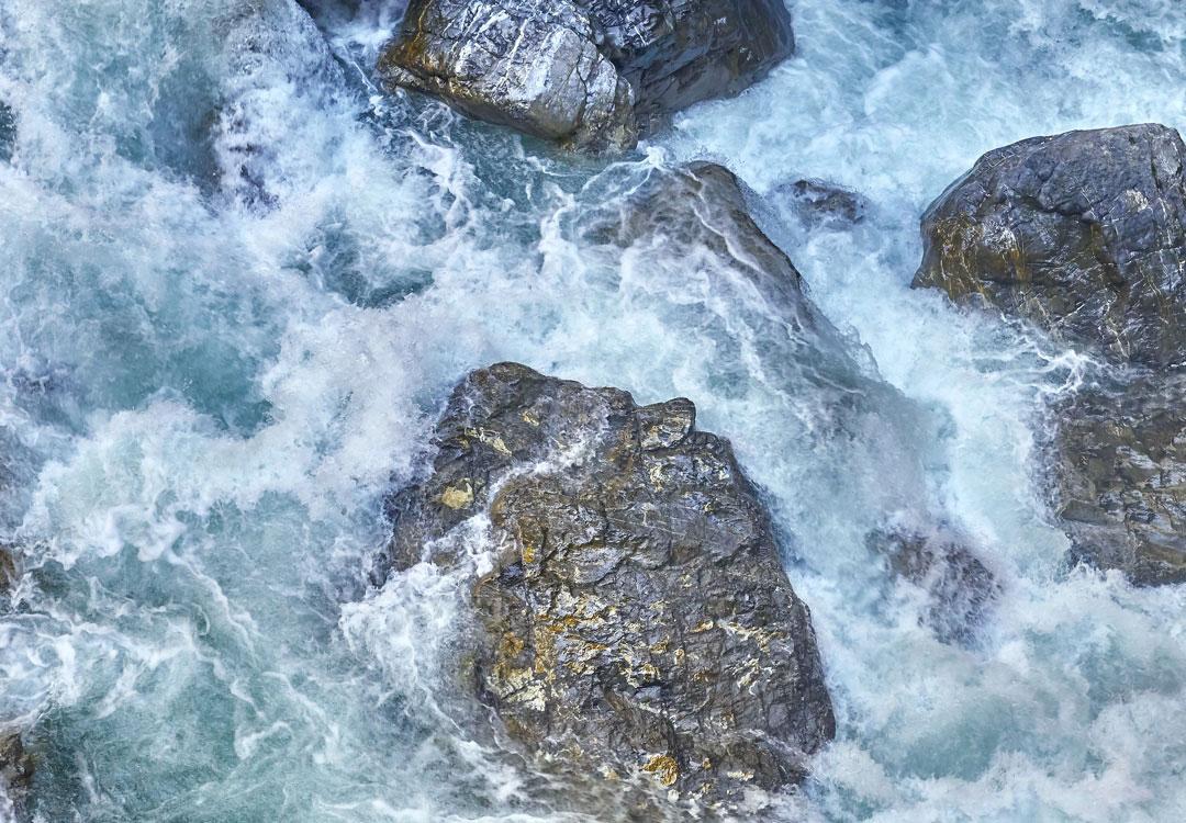 Rwący górski potok z dużymi głazami w korycie z bliska